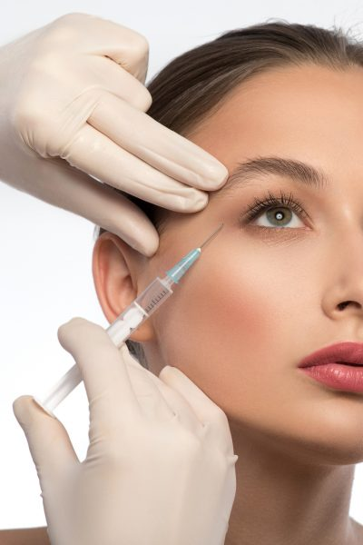 Professional cosmetologist is making botox injection into female eye area. Isolated